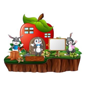 Rotes apfelhaus mit drei kaninchen
