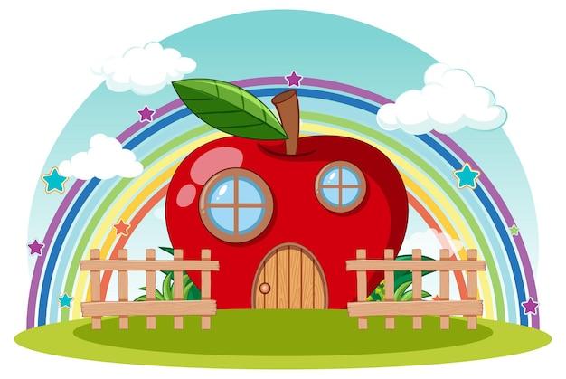 Rotes apfelhaus mit regenbogen am himmel