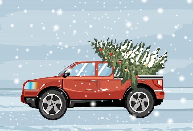 Rotes auto, das den immergrünen tannenbaum bedeckt im schnee trägt