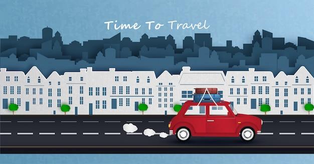 Rotes auto fährt in der hauptstadt und fährt weg von der stadt.