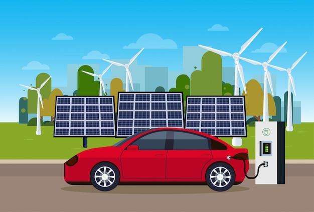 Rotes elektroauto, das an der station von den wind-trurbines und von den sonnenkollektor-batterien eco freundliches vechicle-konzept auflädt
