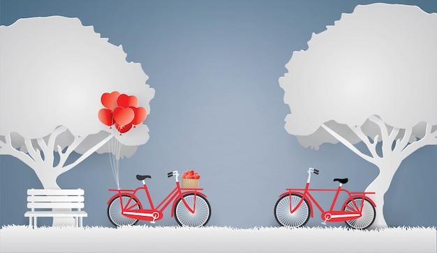 Rotes fahrrad und herz im korb unter dem baum.