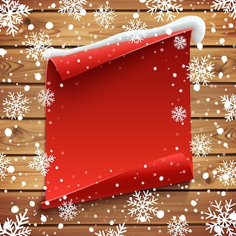 Rotes, gebogenes papierbanner auf holzbrettern mit schnee und schneeflocken. weihnachtsgrußkartenschablone.