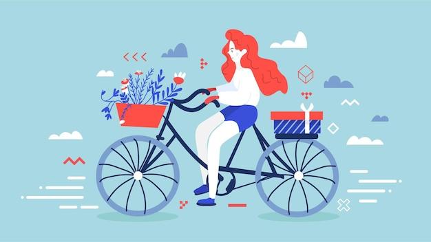 Rotes mädchen, das auf dem fahrrad verziert, verziert blumenkorb und geschenkbox hinter ihr.