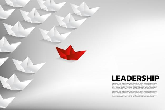 Rotes origami papierschiff, welches die gruppe von weiß führt. geschäftskonzept der teamführung