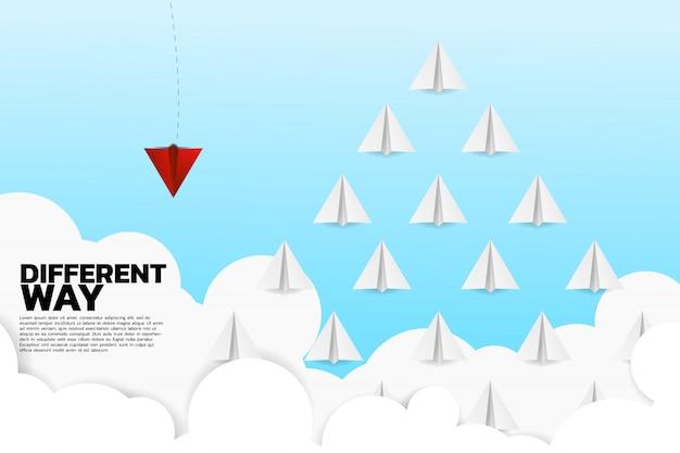 Rotes origamipapierflugzeug geht unterschiedliche weise von der gruppe von weiß