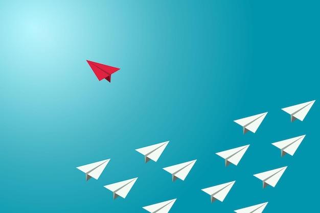 Rotes papierflugzeug änderte die richtung von einer gruppe weißer flugzeuge