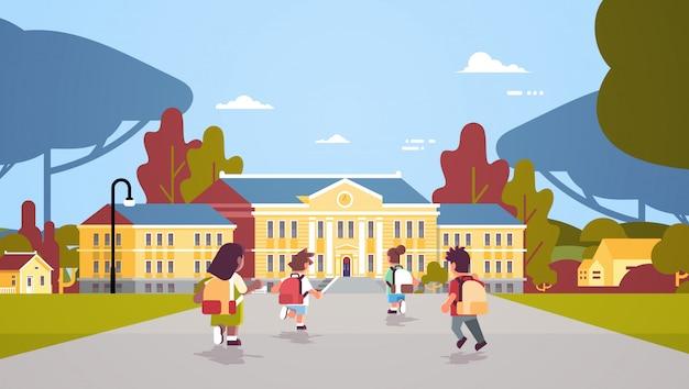 Rückansicht kindergruppe mit rucksäcken, die zurück zum schulbildungskonzept laufen, mischen rennschüler vor gebäudelandschaftshintergrund flach in voller länge horizontal
