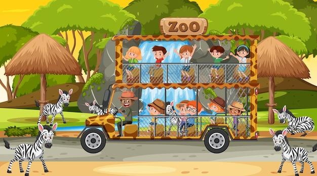 Safari bei sonnenuntergang mit kindern, die eine zebragruppe beobachten