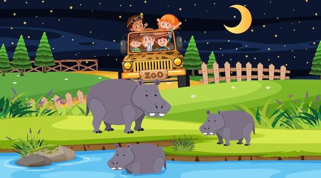 Safari in der nachtszene mit vielen kindern, die eine nilpferdgruppe beobachten?