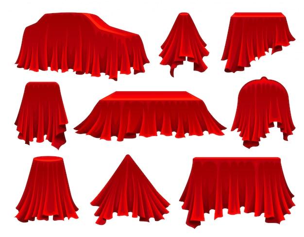 Sammlung von gegenständen unter rotem stoff versteckt.