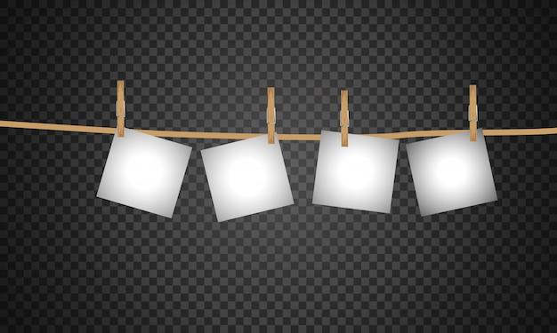 Sammlung von leeren fotorahmen, die durch wäscheklammern an einem seil hängen.