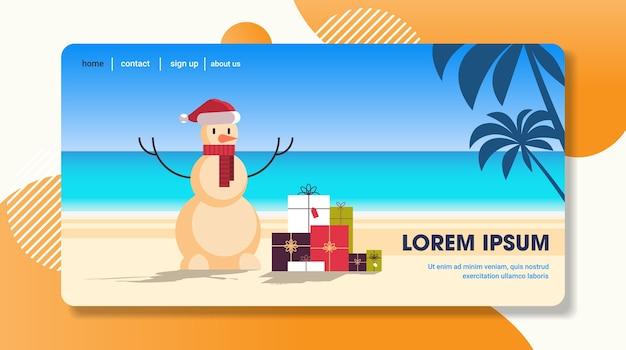 Sandiger weihnachtsschneemann mit geschenkgeschenkboxen frohes neues jahr urlaubsurlaub feierkonzept tropischer strand seelandschaftslandeseite