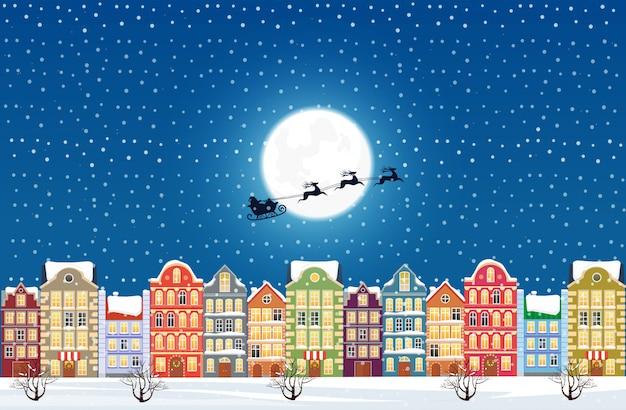 Santa claus fliegt über eine verzierte schneebedeckte alte stadtstadt am weihnachtsabend.