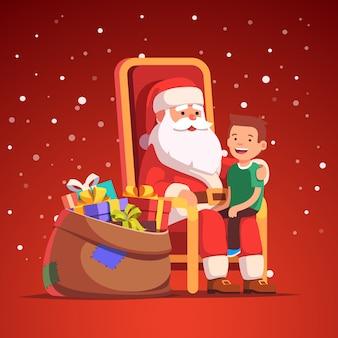 Santa claus hält kleinen lächelnden jungen auf seinem schoß