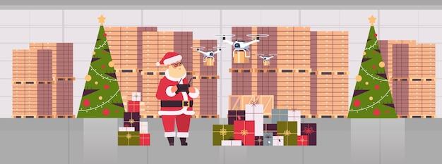 Santa claus holding entfernen controller-drohne mit geschenkgeschenkboxen, die im modernen lagerinneren-weihnachtsfeiertagsfeierkonzept fliegen