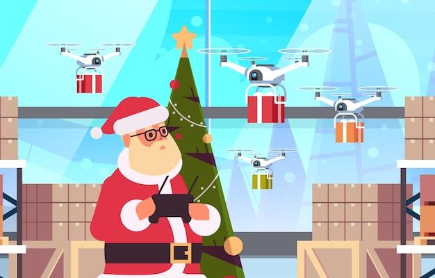 Santa claus holding entfernen controller-drohne mit geschenkgeschenkboxen, die in der modernen lagerhausinnenweihnachtsfeiertagsfeier fliegen