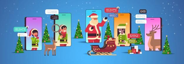 Santa claus mit elfen-helfern, die chat-app soziale netzwerkkommunikation neujahrsfeiertagsfeierkonzept verwenden