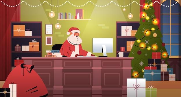 Santa claus sitzt am arbeitsplatz und verwendet computer frohe weihnachten frohes neues jahr feiertagsfeier konzept dekoriert büro interieur horizontale vektor-illustration