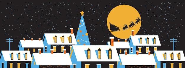 Santa fliegt im schlitten mit rentieren im nachthimmel über schneebedeckten dorfhäusern frohe weihnachten winterferien konzept grußkarte flach horizontal