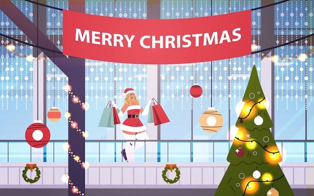 Santa frau mit geschenken, die im einkaufszentrum gehen, verziert für frohe weihnachten und neujahrswinterferienfeier großen ladeninnenraum horizontale vektorillustration in voller länge