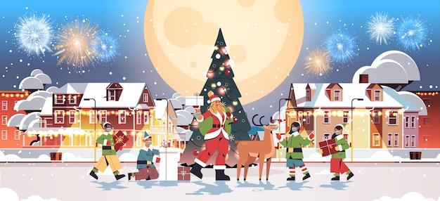 Santa frau stehend mit hirsch und mischen rasse elfen in masken neujahr frohe weihnachten feiertagsfeier grußkarte feuerwerk in nachthimmel stadtbild hintergrund voller länge horizontale vektor illustra