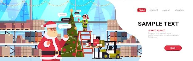 Santa mit männlichem elfenhelfer, der mit der mobilen app auf der chat-blasenkommunikation des sozialen netzwerks des smartphones chattet