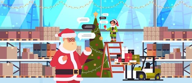 Santa mit männlichem elfenhelfer, der unter verwendung der mobilen app auf chat-blasenkommunikationskonzept des sozialen netzwerks des smartphones modernes lagerhaus-innenporträt horizontale vektorillustration chattet