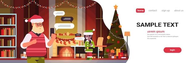 Santa mit weiblichem elfenhelfer, der unter verwendung der mobilen app auf chat-blasenkommunikation des sozialen netzwerks des smartphones chattet
