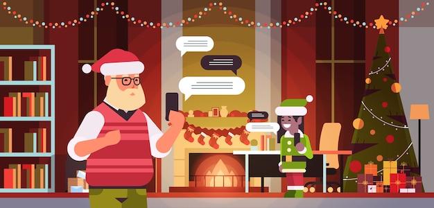 Santa mit weiblichem elfenhelfer, der unter verwendung der mobilen app auf chat-blasenkommunikationskonzept des sozialen netzwerks des smartphones modernes wohnzimmerinnenporträt horizontale vektorillustration chattet