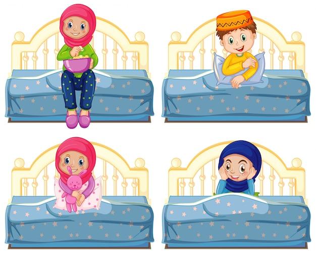 Satz arabische muslimische kinder in der traditionellen kleidung, die auf einem bett lokalisiert sitzt
