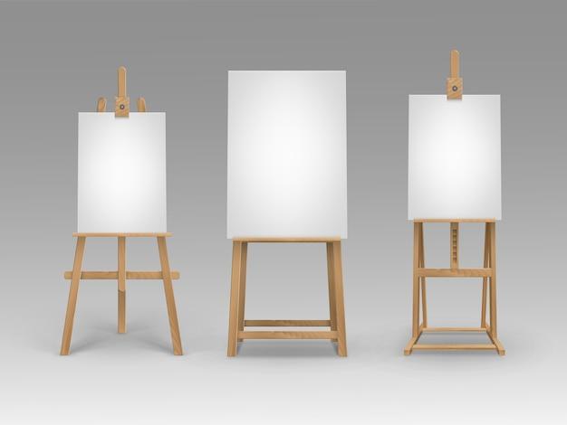 Satz braune sienna-hölzerne staffeleien mit leeren leeren vertikalen leinwänden des modells, die auf hintergrund isoliert werden