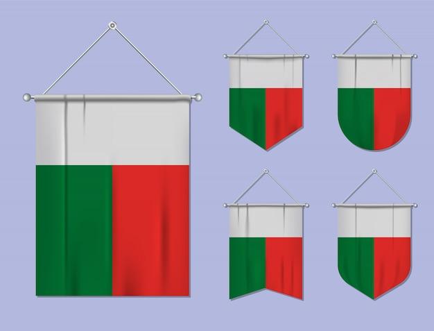 Satz hängende flaggen madagaskar mit textilbeschaffenheit. diversitätsformen des nationalflaggenlandes. vertikaler schablonenwimpel