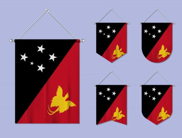 Satz hängende flaggen papua-neuguinea mit textilbeschaffenheit. diversitätsformen des nationalflaggenlandes. vertikaler schablonenwimpel.