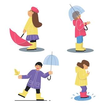 Satz kinder am regnerischen tag. jungen und mädchen mit regenschirmen im herbst.