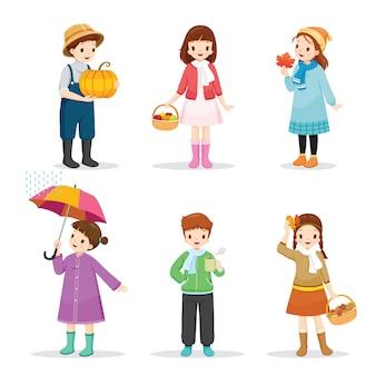 Satz kinder, die verschiedene kleidung für die herbstsaison tragen