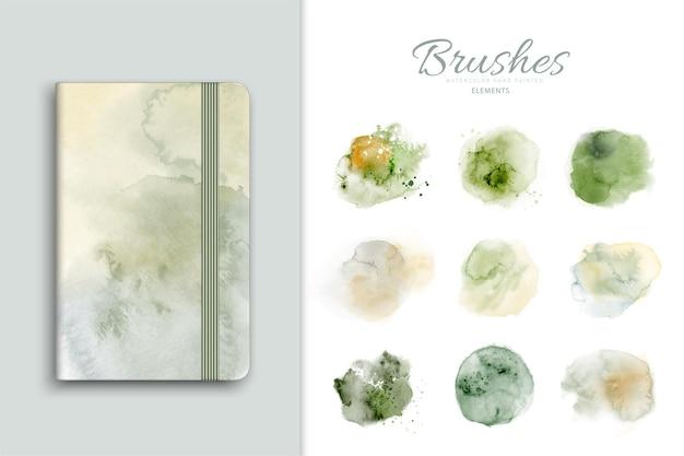 Satz kunst färbt grünen aquarell-spritzer, der handgemalt ist. fleckenspritzaquarell, das als element in der dekorativen gestaltung mit notizbuch verwendet wird