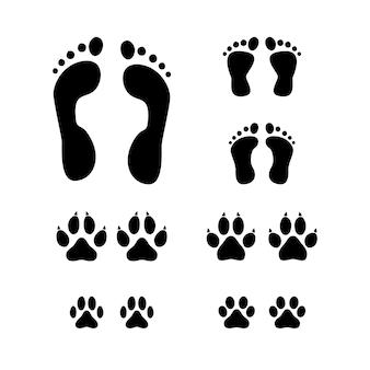 Satz schwarzer tierpfotenabdruck und menschlicher und kinderfußabdruck lokalisiert auf weißem hintergrund.