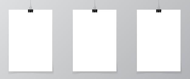 Satz von 2 leeren plakaten, die an einem faden mit schwarzen klammern gegen eine wand als minimalistisches stilportfolio, galeriepräsentationskonzept hängen. 3d-illustration