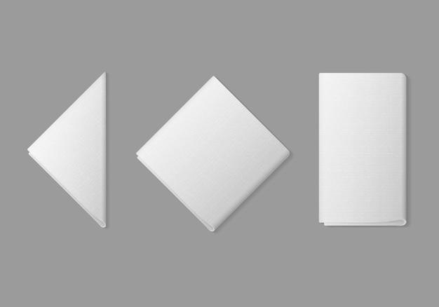 Satz weiße gefaltete quadratische rechteckige dreieckige servietten draufsicht auf hintergrund. sitzordnung bei tisch