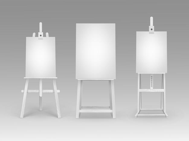Satz weiße hölzerne staffeleien mit mock-up-leeren leeren vertikalen leinwänden, die auf hintergrund lokalisiert werden