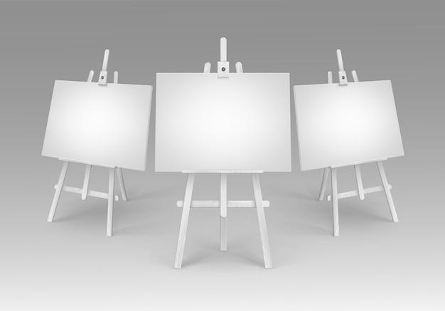 Satz weiße hölzerne staffeleien mit schein leeren leeren leinwänden lokalisiert auf hintergrund
