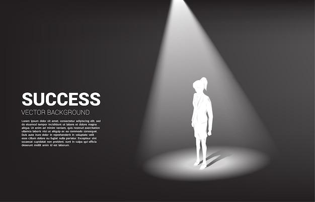 Schattenbild der geschäftsfrau, die im scheinwerferlicht steht. geschäftskonzept
