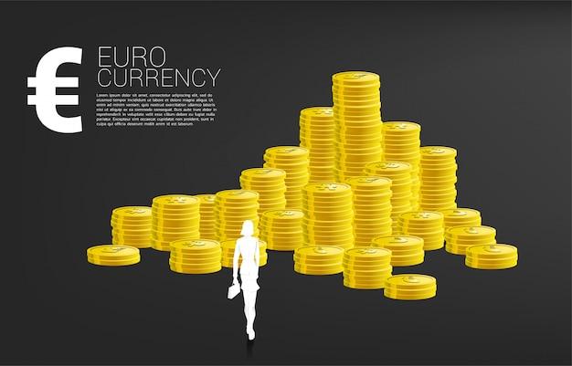 Schattenbild der geschäftsfrau mit dem aktenkoffer, der vor eurogeld und stapel der münze steht. konzept des erfolgsgeschäfts und der wirtschaft der eurozone.