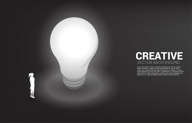 Schattenbild der geschäftsfrau stehend mit glühlampe. geschäftskonzept der kreativen idee und der lösung.
