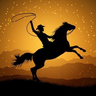 Schattenbild des cowboys mit lasso auf dem aufziehen des pferds