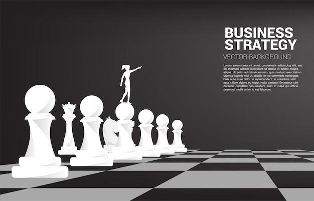 Schattenbild des geschäftsfraupunktes vorwärts mit schachfigur. konzept des geschäftsstrategie-marketings.