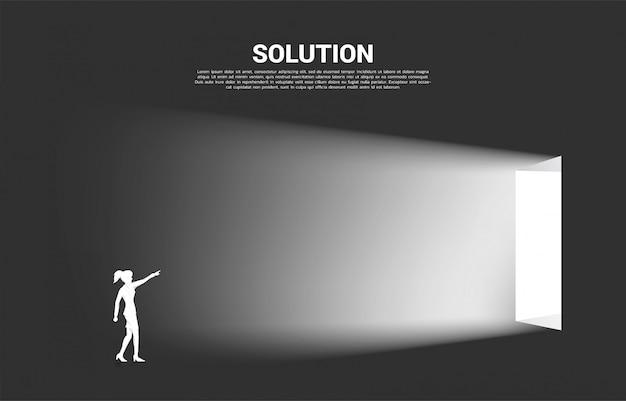Schattenbild des geschäftsfraupunktes vorwärts zur ausgangstür. konzept der start- und geschäftslösung.