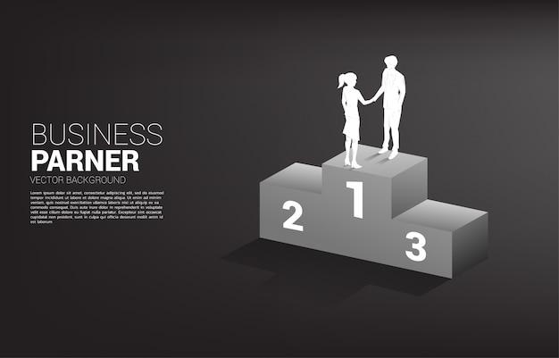 Schattenbild des geschäftsmann- und geschäftsfrau-handshakes oben auf dem podium. konzept der teamarbeit partnerschaft und zusammenarbeit.