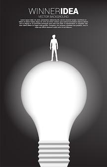 Schattenbild des geschäftsmannes, der auf glühbirne steht